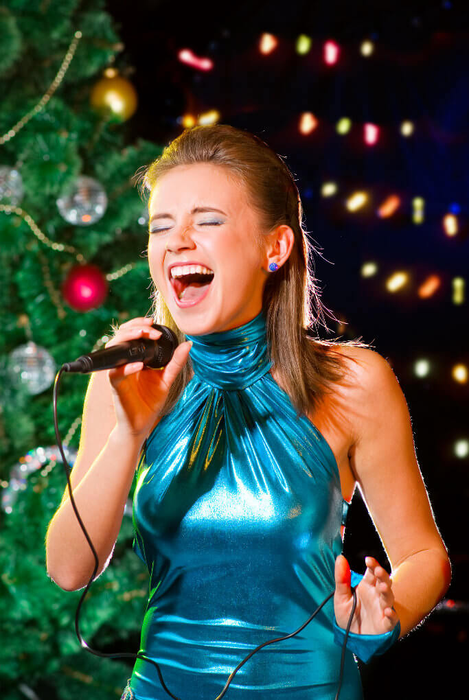Young woman singing karaoke near a Christmas tree