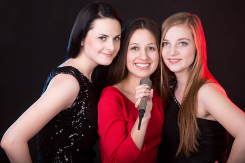 Portrait of three elegant beautiful girls posing with microphone happy smiling in colorful light of spotlights